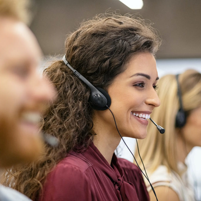 Smiling woman call center operator doing her job with a headset while working on computer. Positive smiling agents in conversation with customer over headset, sitting in row. Consulting and assistance helpdesk service.